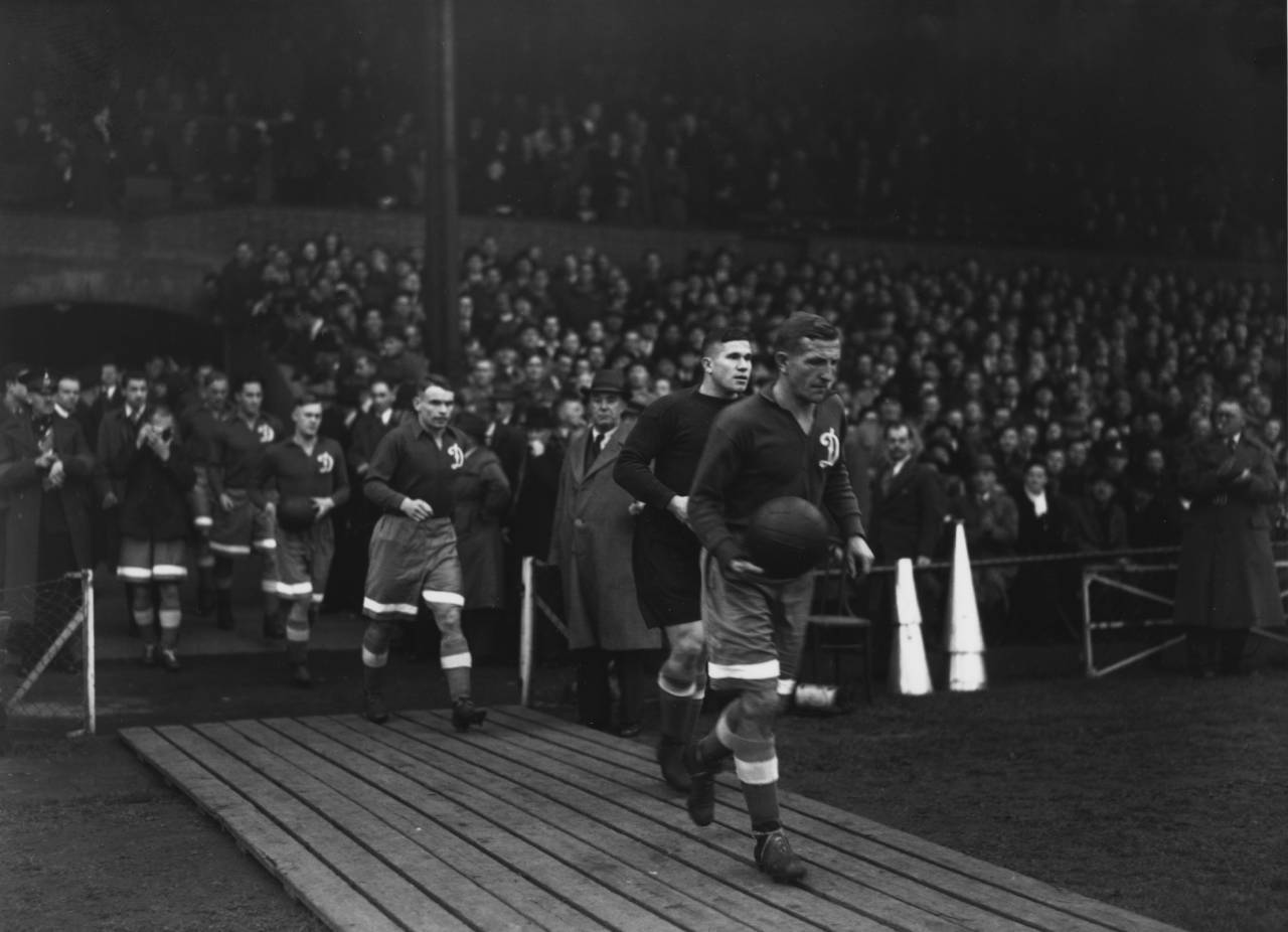 13 NOV 1945: RUSSIAN FOOTBALL TEAM MOSCOW DYNAMO WALK OUT ONTO THE PITCH BEFORE THEIR MATCH AGAINST CHELSEA AT STAMFORD BRIDGE. IT IS THE DYNAMOS FIRST VISIT TO GREAT BRITAIN AND AN ESTIMATED 100,000 PEOPLE TURNED UP TO WATCH THE MATCH. THE SHEER WEIGHT OF THE CROWD BROKE DOWN ALL THE GATES OF THE GROUND. THE GAME ENDED IN A 3-3 DRAW. Mandatory Credit: Allsport Hulton/Archive