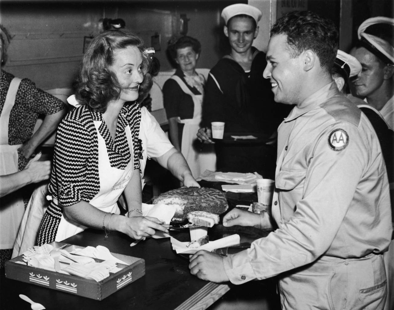 American actor Bette Davis (1908 - 1989) smiles as she serves a slice of cake to US Army private Vazquez while helping Allied troops in the Stage Door Canteen, New York City, July 10, 1943. (Photo by Hulton Archive/Getty Images)