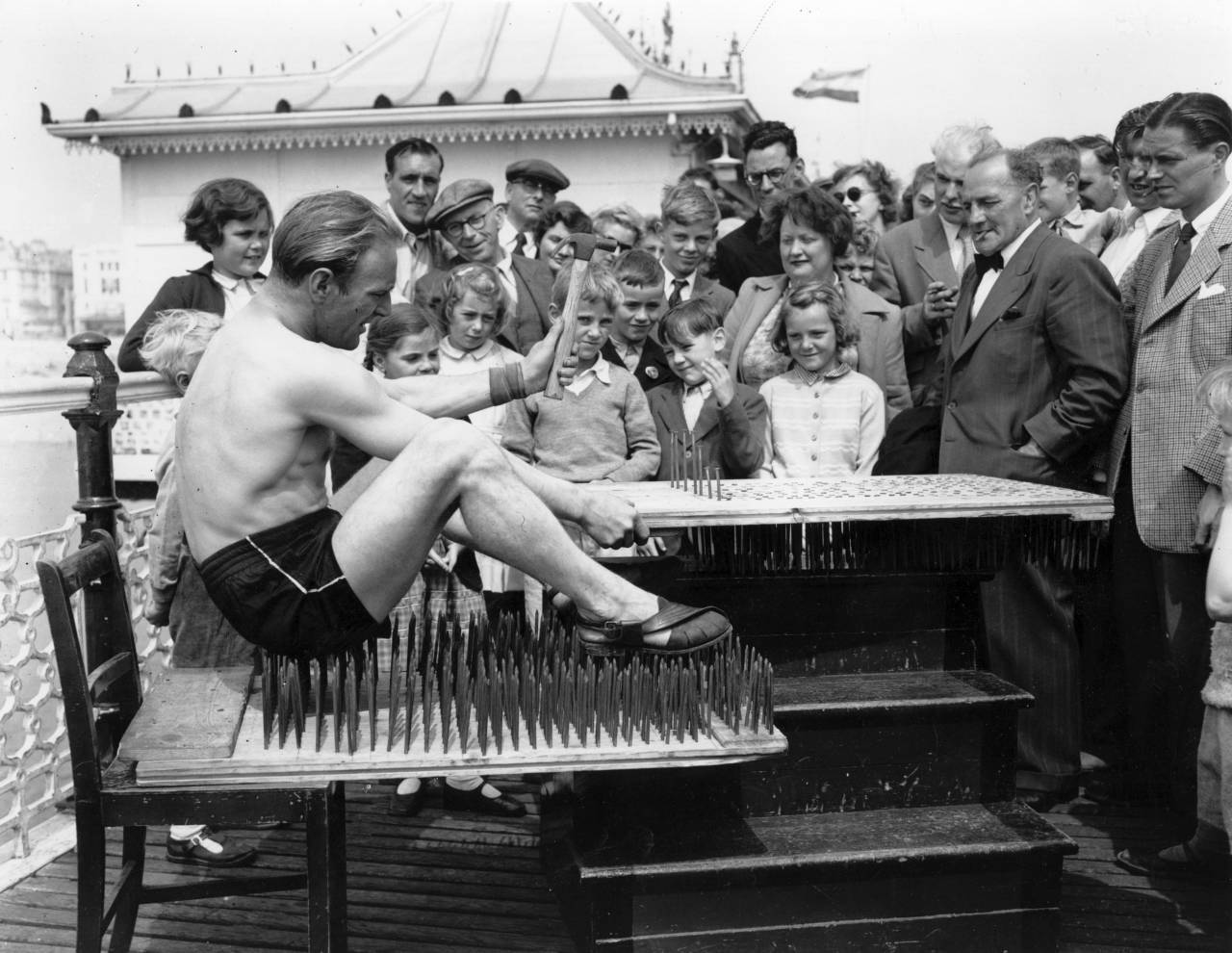 Stunt man Michael Blondini puts the finishing touches to his bed of nails on the Palace Pier, Brighton. (Photo by Keystone/Getty Images)