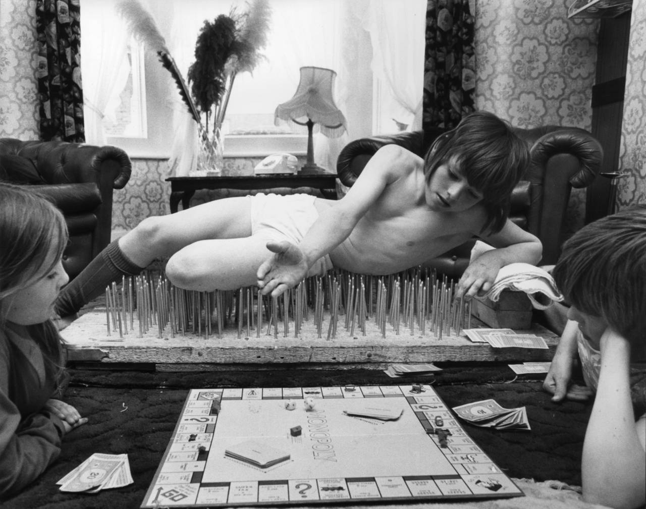 Eight-year-old Mark Harman from London enjoying a game of Monopoly with his brother Graham and sister Belinda, from his bed of nails. Mark is being trained by world Champion Roy Singfield and spends two hours every other evening relaxing on his nail bed. (Photo by Ian Tyas/Getty Images)