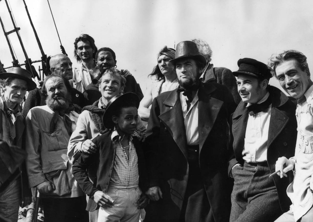 The cast and crew of the Warner Brothers film 'Moby Dick' on location in Youghal, County Cork. Members include Richard Basehart, Gregory Peck (1916 - 2003) as Captain Ahab, Leo Genn (1905 - 1978) in the sailor's cap, and director John Huston (1906 - 1987) on the far right. (Photo by Fox Photos/Getty Images)