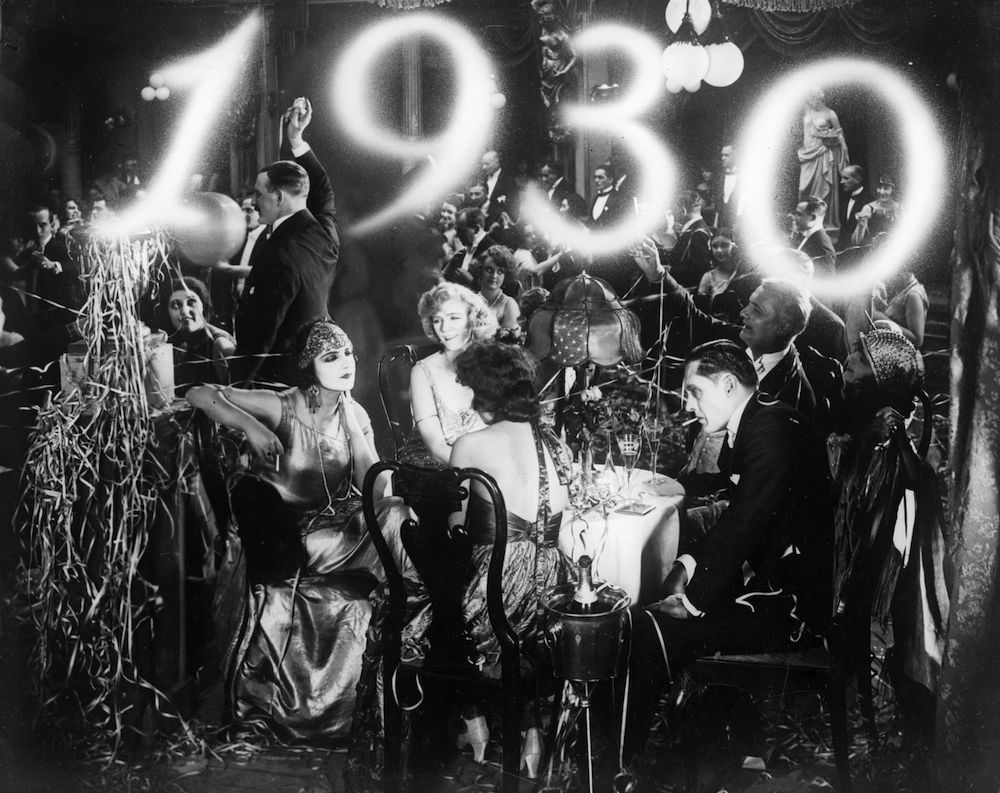 1930: Streamers and champagne for revellers at a New Year's party. (Photo by General Photographic Agency/Getty Images)