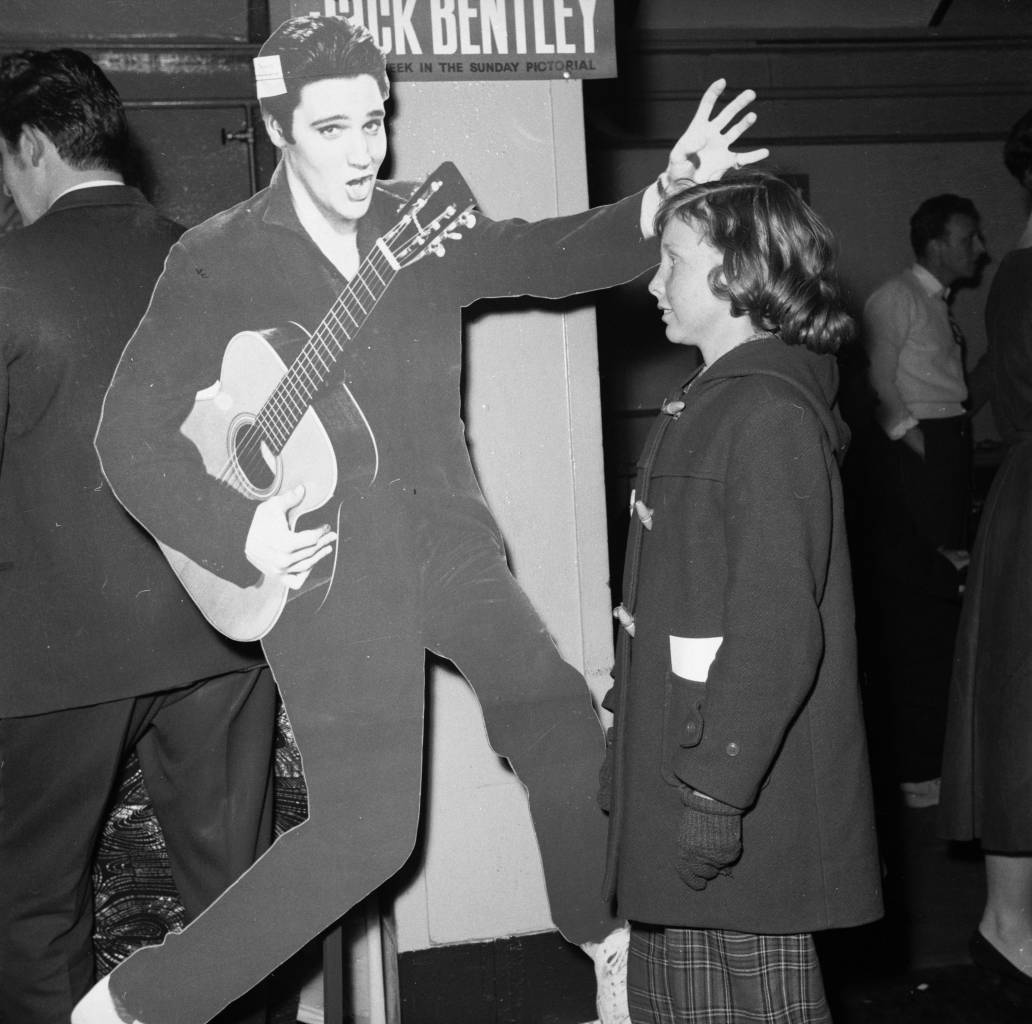 February 1958: 18 year old Elvis fan Lillie Cooper of Tollworth in Surrey staring at a life-size cardboard cut-out of Elvis Presley, a prize in a raffle to be drawn at the rock 'n' roll contest at Wimbledon Palais in London. (Photo by Rosemary Matthews/BIPs/Getty Images)