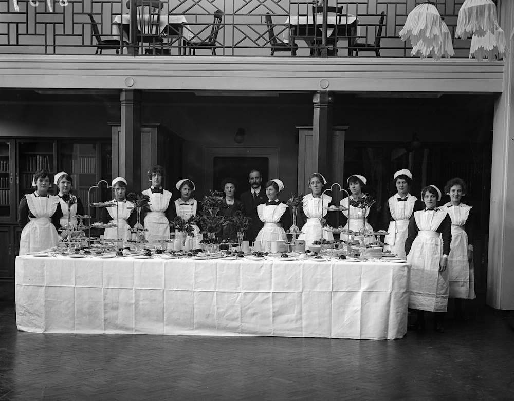 October 1918: A table is laden with cakes and the staff are ready to serve at the graduation ceremony for women students at King's College Medical School. (Photo by Topical Press Agency/Getty Images)