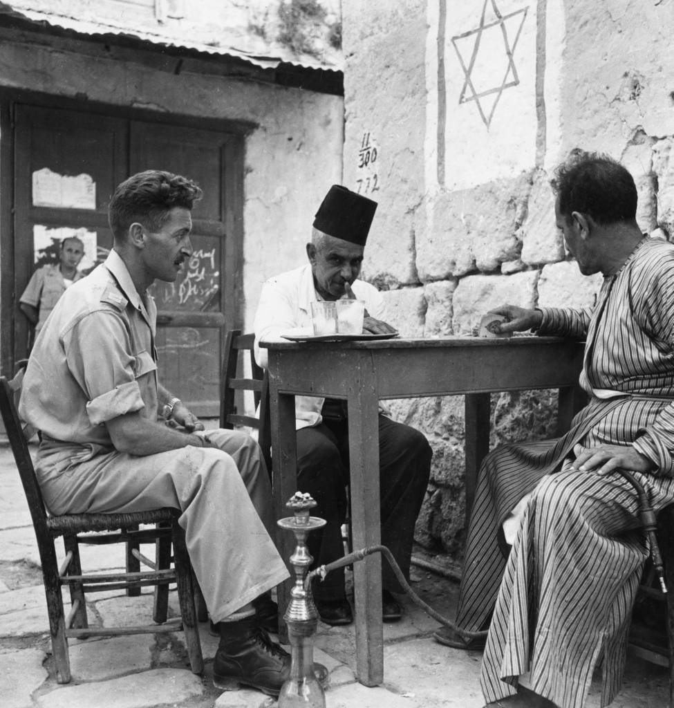 circa 1937: A Jewish soldier and two Arab tradesmen enjoy a game of cards in the town of Madjdal at the entrance to the Negev. On the wall above them is painted the Star of David and one of the Arabs is holding a hookah. (Photo by George Pickow/Three Lions/Getty Images)