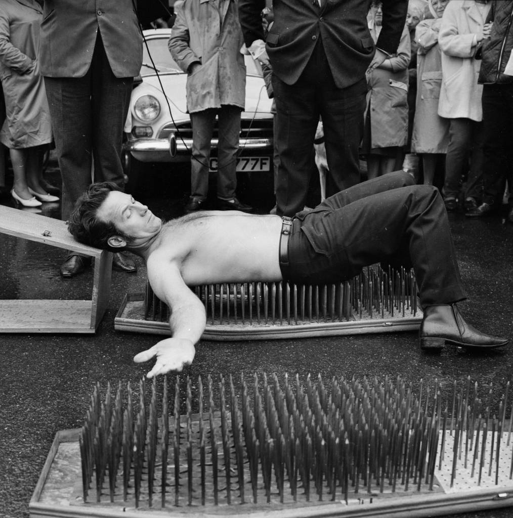 27th September 1968: Kenyan stuntman Jackie Paul lying on a bed of nails in front of a crowd at Weymouth. (Photo by C. Woods/Express/Getty Images)