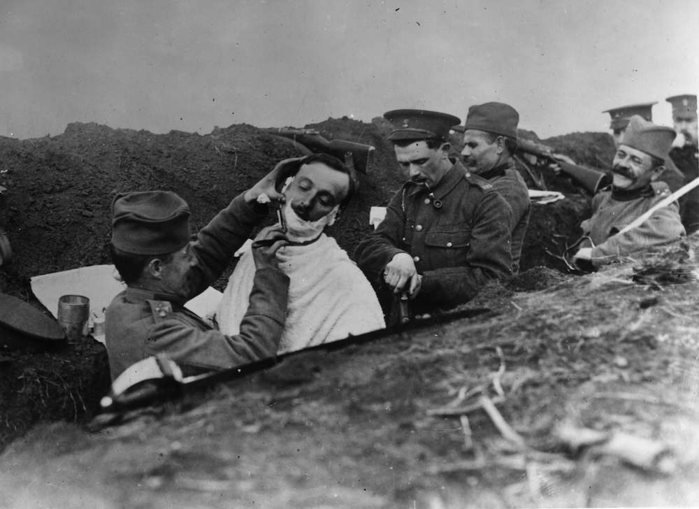 circa 1916: A Serbian soldier being shaved in a trench by one of his comrades. 'Scenes with our Serbian allies.' 'La Toilet' in a trench. (Photo by Topical Press Agency/Getty Images)