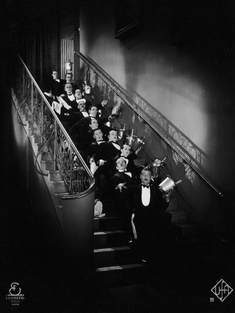 circa 1920: A line of waiters carrying bottles of champagne in coolers fall up a flight of stairs. (Photo by Hulton Archive/Getty Images)