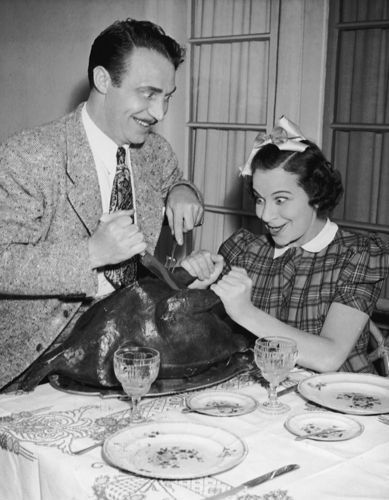 circa 1945: American actor, singer and comedian Fanny Brice helps British radio actor Hanley Stafford carve a turkey. (Photo by Hulton Archive/Getty Images)