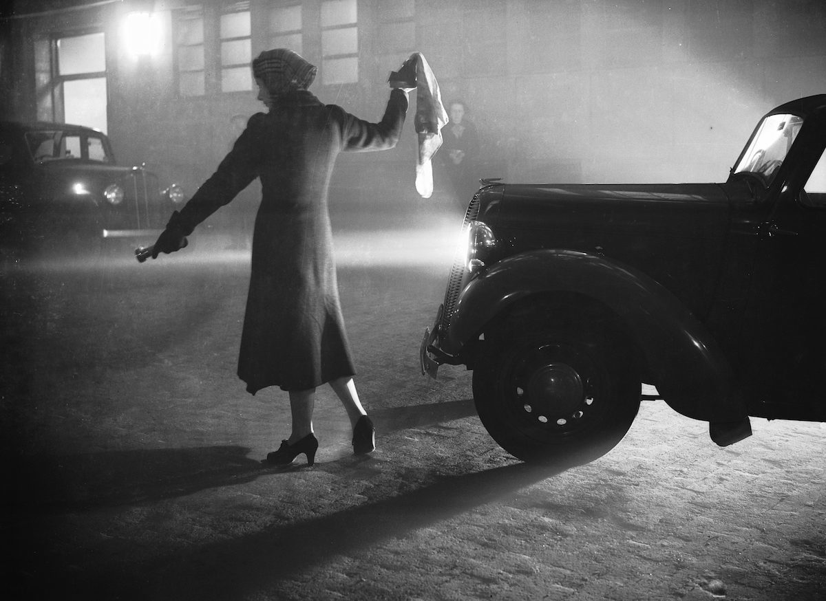 25th October 1938: A woman leads a car through London's Regent's Park with a torch, during the thick fog with visibility reduced to a few yards. (Photo by William Vanderson/Keystone/Getty Images)