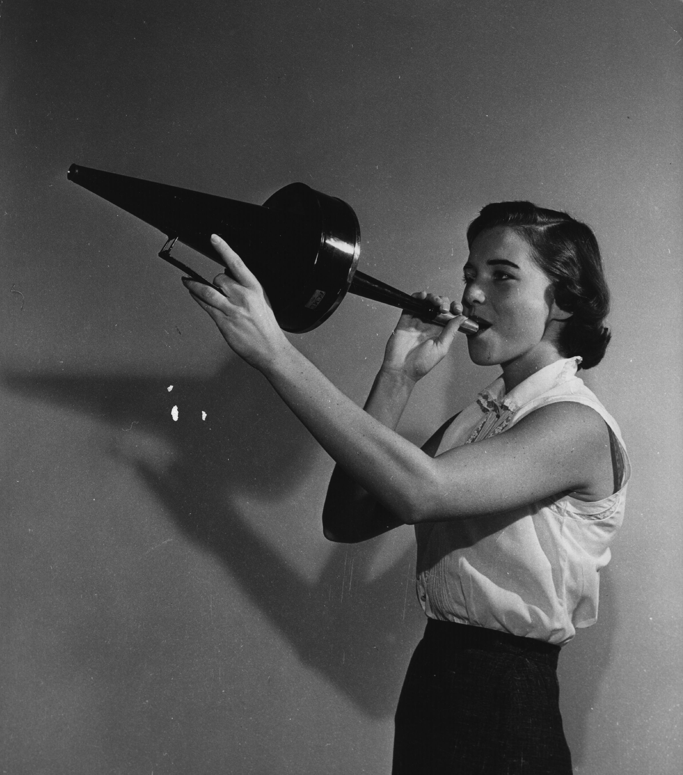 circa 1950: A girl blowing on a fog horn at the Carrell Instrument Services. (Photo by Al Barry/Three Lions/Getty Images)