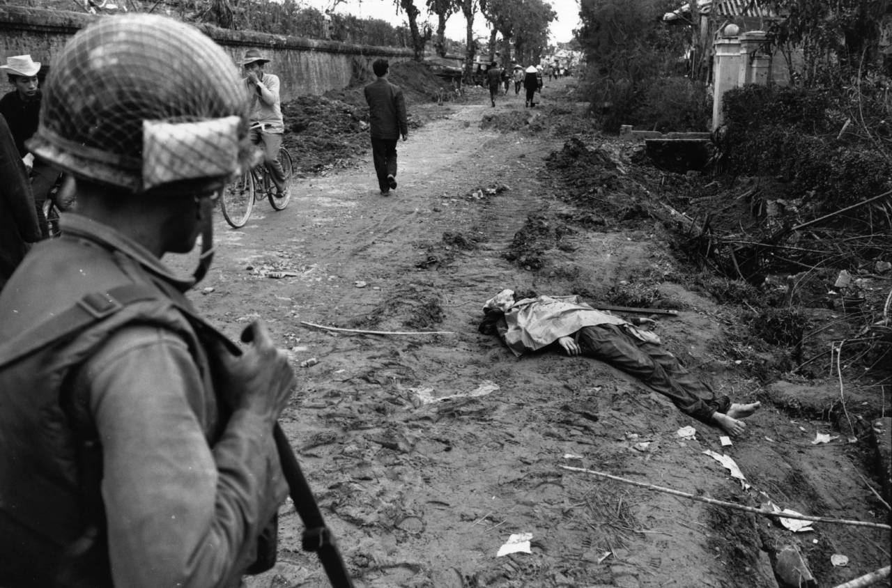 circa 1968: A US GI looks at a dead peasant by a ditch in southeast Asia during the Vietnam War. (Photo by Hulton Archive/Getty Images)
