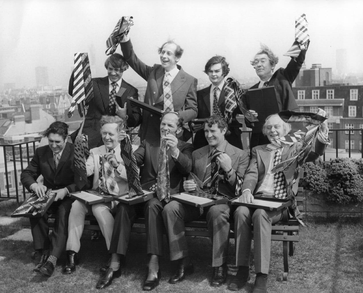 April 1974:  The Top Ten Tiemen celebrate their victory by displaying their winning ties at a presentation at the  Playboy Club, Park Lane.  Standing, left to right:  Leonard Parkin, ITN, Peter Woods, BBC TV, Norman Lamont, MP for Kingston-upon-Thames, Kingsley Amis, Author.  Seated, left to right:  Frank Chapple, General Secretary EETPU, Michael Barratt, BBC-TV, Henry Cooper, Malcolm Allison, Soccer Manager, and Patrick Cargill, Actor.  (Photo by Wesley/Keystone/Getty Images)