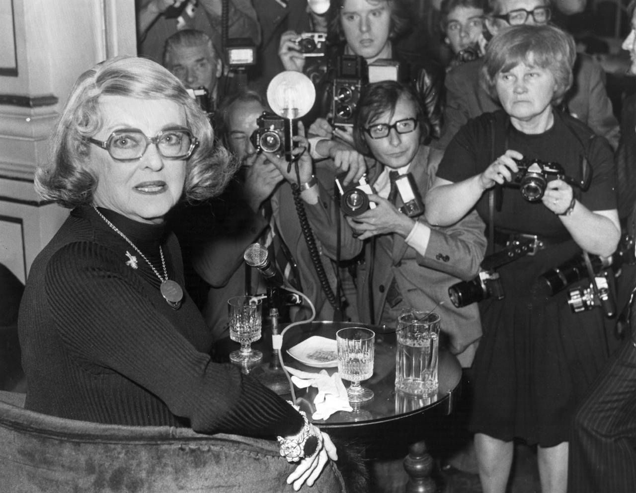 2nd October 1975: Bette Davis (1908-1989), American film actress, at a press conference at the London Palladium, where she will make her stage debut. Amongst the members of the press is photographer Jane Bown. (Photo by Central Press/Getty Images)