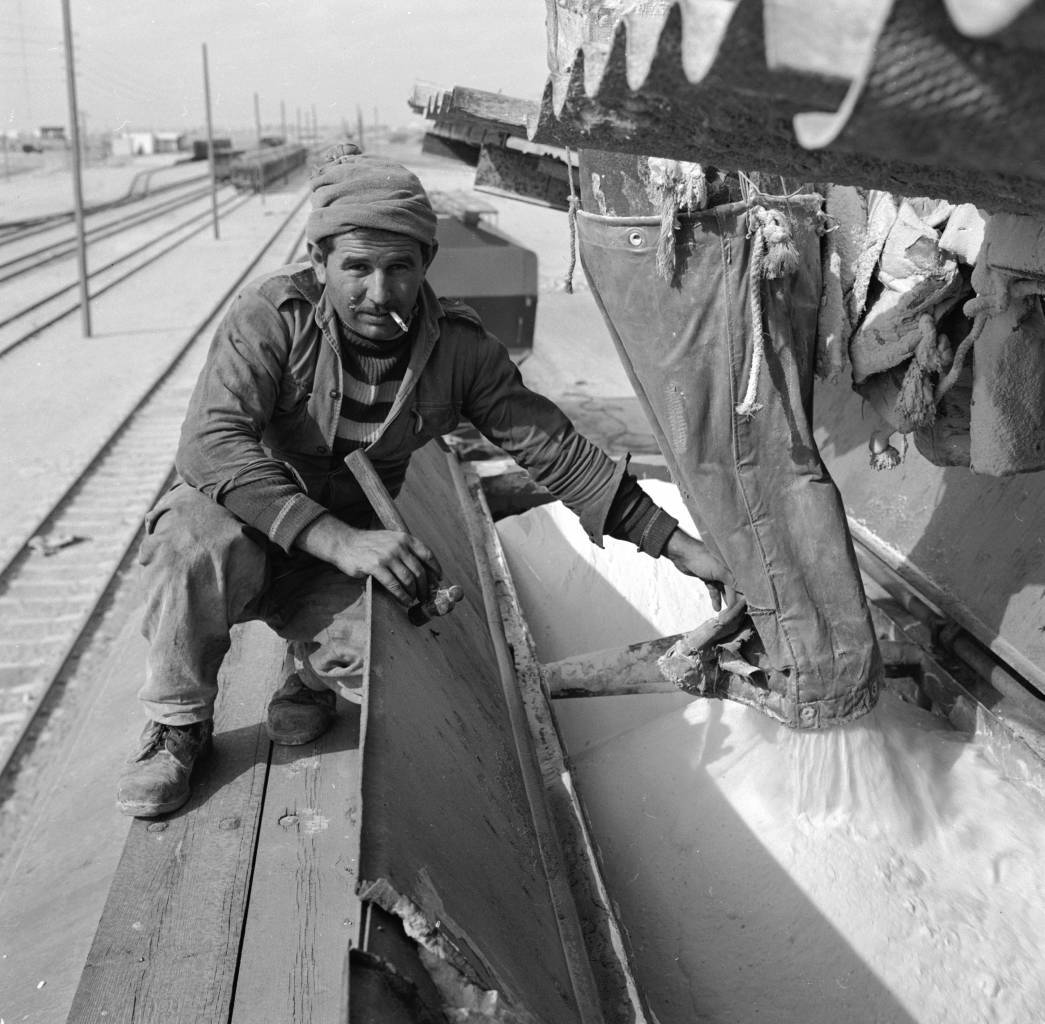 circa 1955: A Moroccan immigrant now living in Beersheba, Israel, loads potash into a railway car. (Photo by Evans/Three Lions/Getty Images)