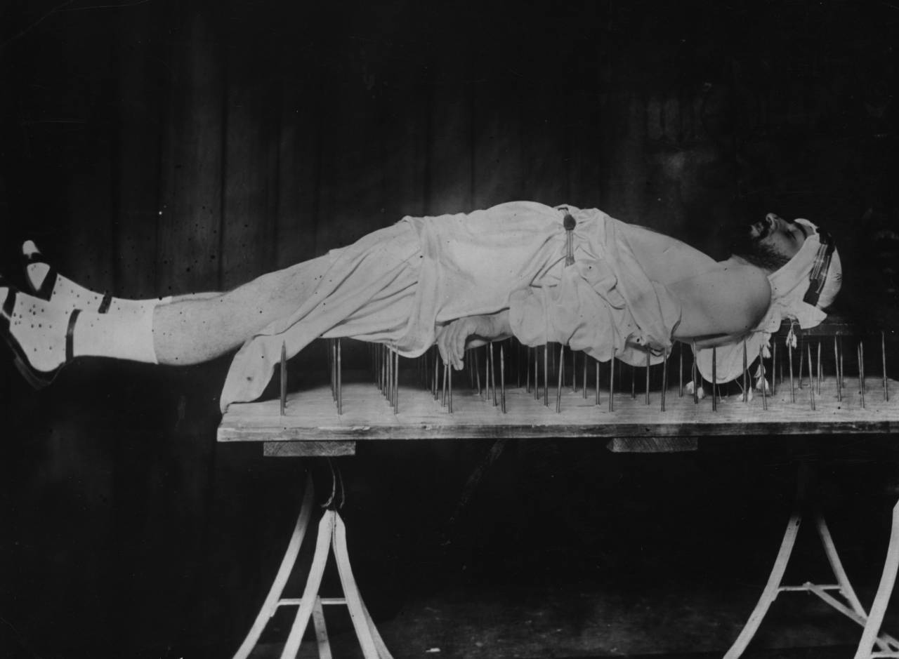 circa 1920: Dr Johra Bey, a Muslim fakir, lying on a bed of nails. (Photo by General Photographic Agency/Getty Images)