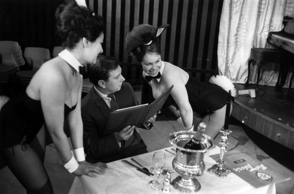 11th February 1963: Two Bunny Girls serving a customer with a champange lunch at London's Playboy Club. (Photo by Victor Blackman/Express/Getty Images)
