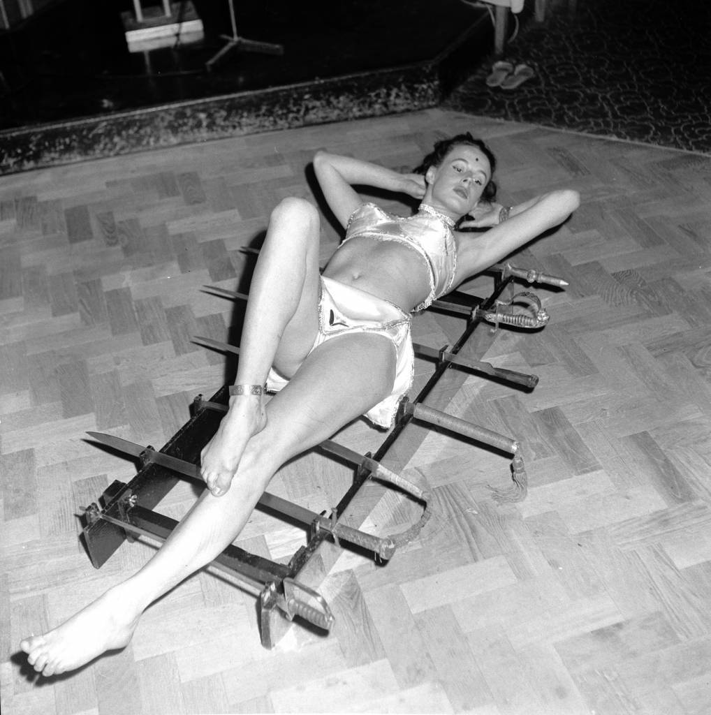 30th July 1956: Heather Boe performs under the name of Rahnee Moti at the Eve Club in London, where she lies on six inch nails and sharp swords. (Photo by Peter Purdy/BIPs/Getty Images)