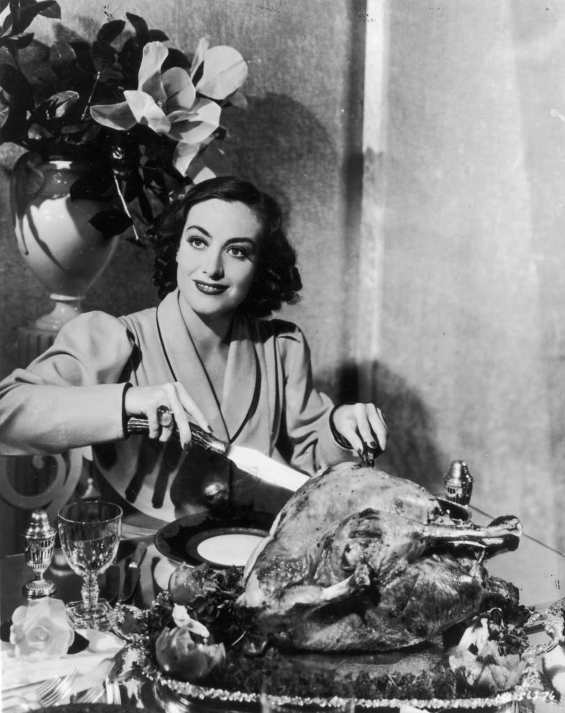 irca 1930: American actress Joan Crawford (1908 - 1977) carving a huge Thanksgiving turkey for a publicity shot. Oddly, movie stars were often requested to strike this pose by their publicists. (Photo by General Photographic Agency/Getty Images)