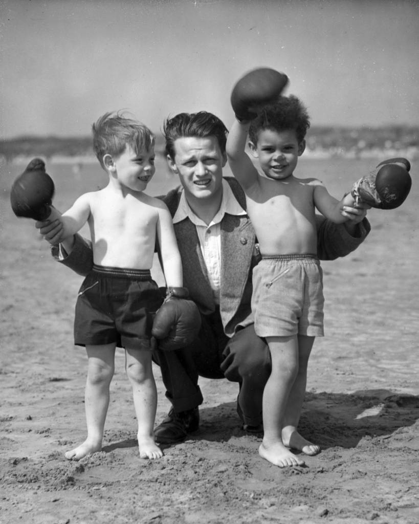 12th July 1954: Chris Davies, leader of the United Nations Boys' Club in Wirral, Merseyside, gives young Billy Feston (left) and Paul Wilson a boxing lesson on the beach. The club aims to give boys from the inner city an opportunity to experience life in a rural holiday camp. (Photo by Kenny Rhodes/Fox Photos/Getty Images)