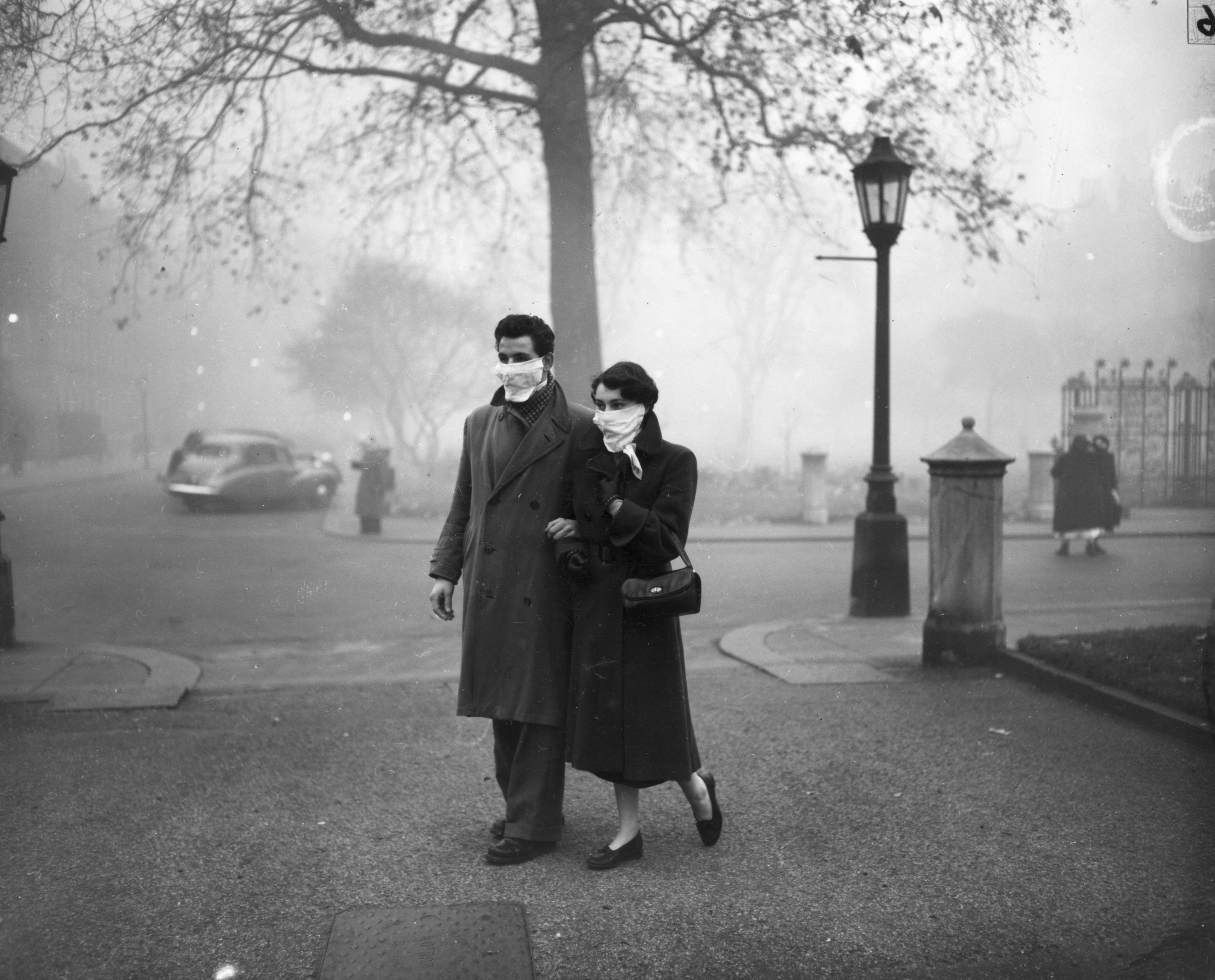 November 1953: A couple walking in London wearing smog masks on a foggy day. (Photo by Monty Fresco/Topical Press Agency/Getty Images)