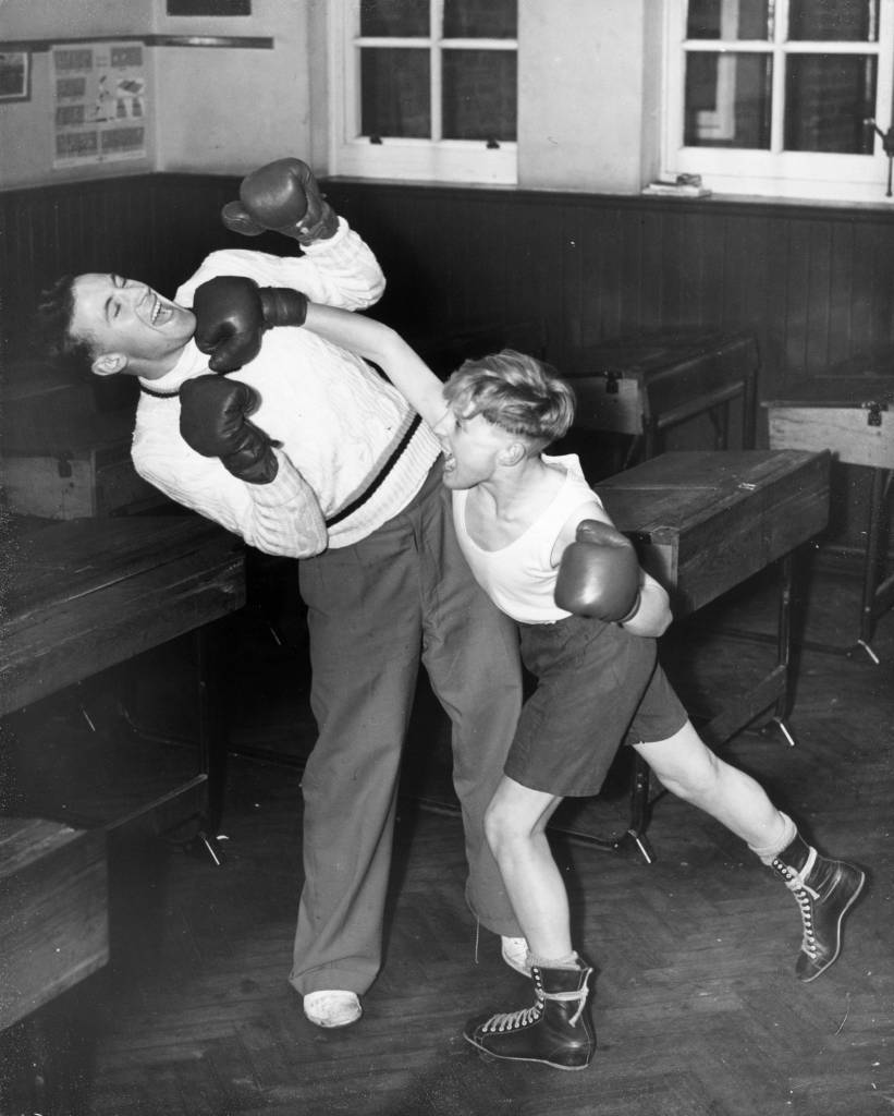 3rd December 1953: Christopher Miles, aged 14, having an after school boxing lesson with one of his teachers at Stepgate School in Chertsey. (Photo by Grierson/Fox Photos/Getty Images)