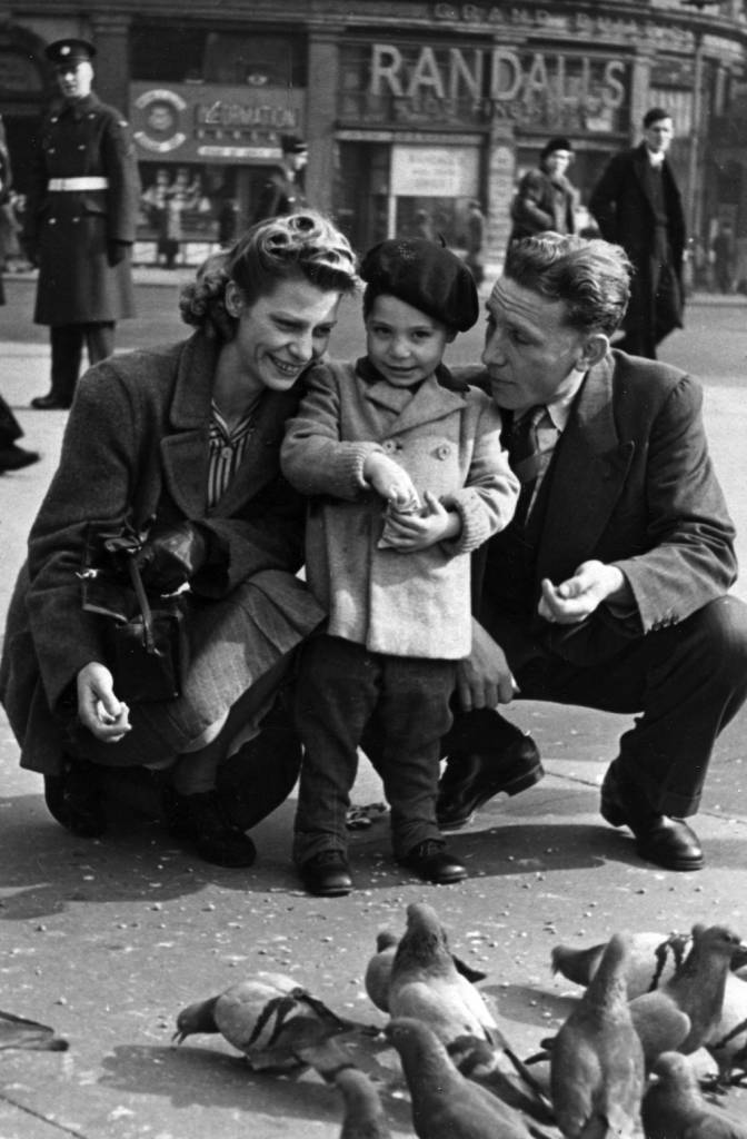 LONDON, UNITED KINGDOM - CIRCA 1943: (EMBARGOED FOR PRINT USAGE UNTIL THURSDAY JULY 2ND 2015) A stylish Charles Robert Watts aged 2 with his mother Lillian and father Charles in Piccadilly Circus in 1943. Charlie was known as Charlie Boy- while his dad was called Charlie. This previously unseen image will form part of The Rolling Stones - 'Exhibitionism' at London's Saatchi Gallery. Mick Jagger, Keith Richards, Charlie Watts and Ronnie Wood have opened their personal archives and found never before seen photographs of themselves as youngsters. These along with hundreds more rare and unseen images will create the first ever international Rolling Stones exhibition which will open at the Saatchi Gallery in April 2016. (Photo by Linda Roots/Getty Images)