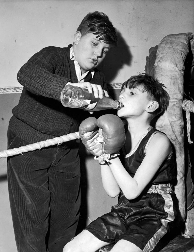 8th February 1956: Eight year old Tony Kelly having a drink between rounds, with the help of his second Brian King, at the Leyton Boxing Club. (Photo by Derek Berwin/Fox Photos/Getty Images)