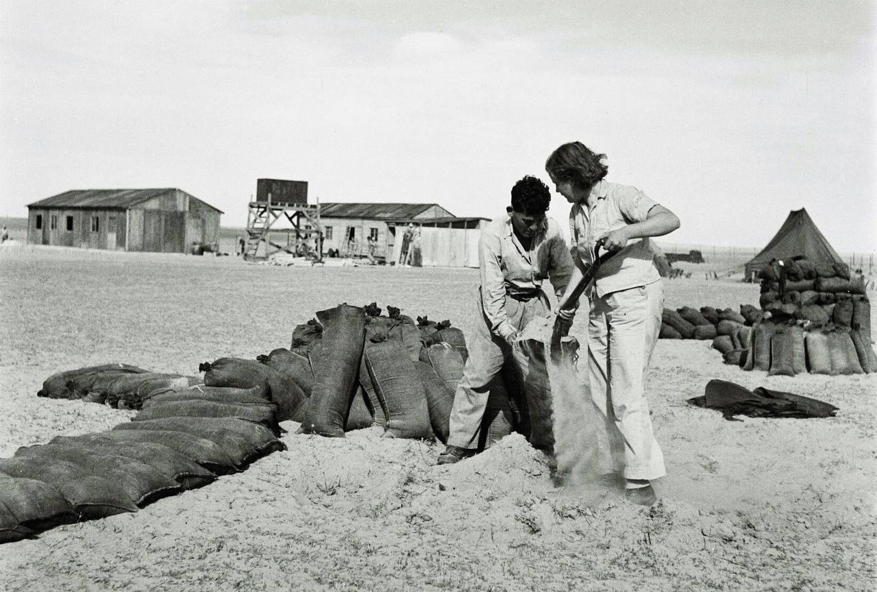 MOSHAV MIVTAHIM, MANDATE PALESTINE - FEBRUARY 1: In this handout from the GPO, Jewish pioneering settler fill sandbags to protect their cooperative farming community February 1, 1947 of Moshav Mivtahim in the Western Negev Desert, during the British Mandate of Palestine, in what would later become the State of Israel. (Photo by Zoltan Kluger/GPO via Getty Images)