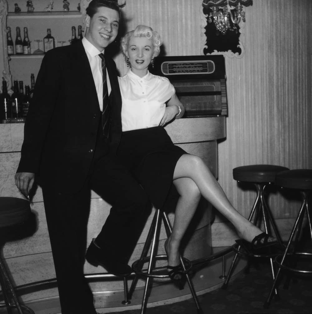 Ruth Ellis (1926 - 1955) at a bar with a friend, 1954. The setting is probably The Little Club, Knightsbridge, which she managed at the time. The following year, Ellis was convicted of the murder of her lover, David Blakely, and hanged at Holloway Prison, becoming the last woman to receive the death penalty in Britain. (Photo by Hulton Archive/Getty Images)
