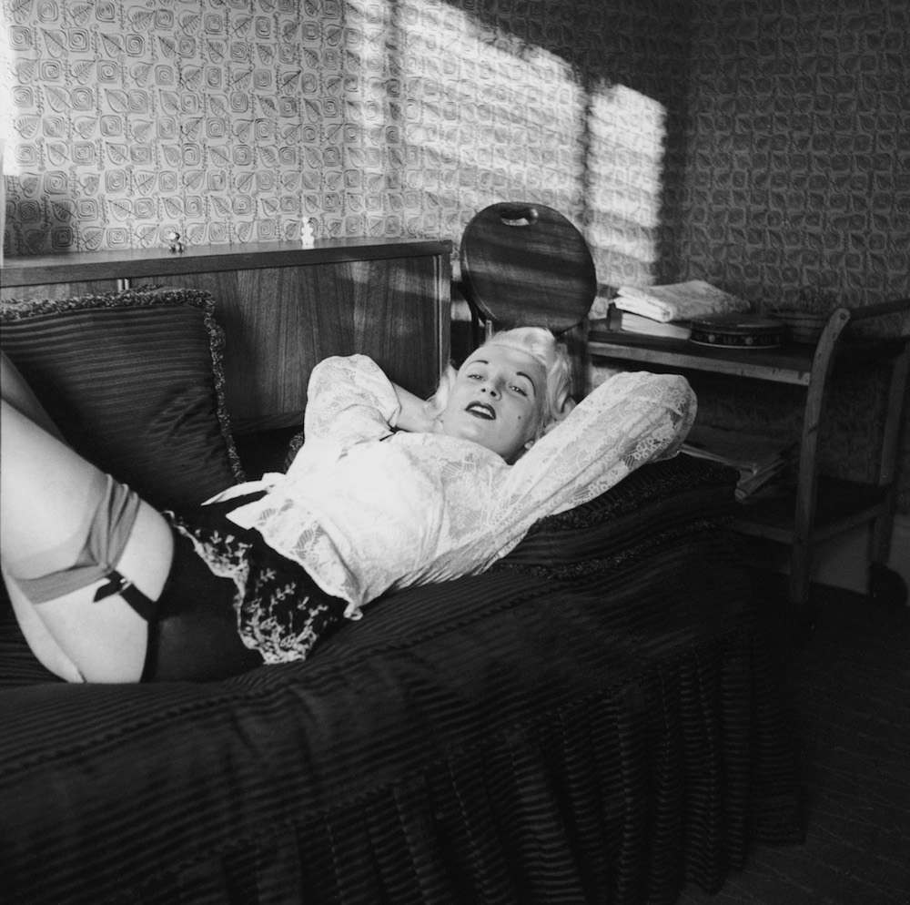 Night club manageress Ruth Ellis (1926 - 1955) poses in stockings and suspenders for one Captain Ritchie, 1954. The setting is probably the flat above her club on the Brompton Road in Knightsbridge, London. In 1955, Ellis was convicted of the murder of her lover, David Blakely, and hanged at Holloway Prison, becoming the last woman to receive the death penalty in Britain. (Photo by Hulton Archive/Getty Images)