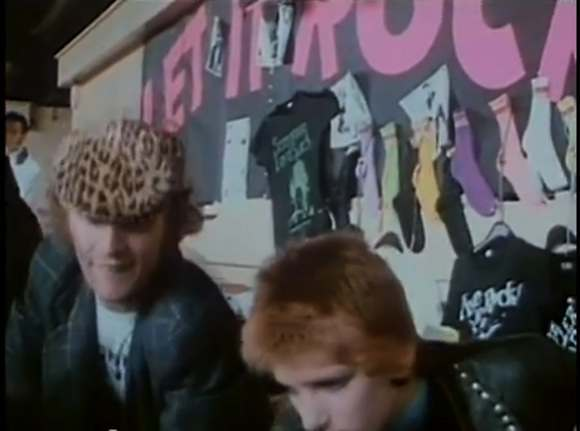 //Malcolm McLaren in leopard print cap with Yvonne Gold serving customers. Note the glitter Screaming Lord Sutch and Vive Le Rock t-shirts pinned to the display board. Still from Peter Clifton's London Rock N Roll Show. //