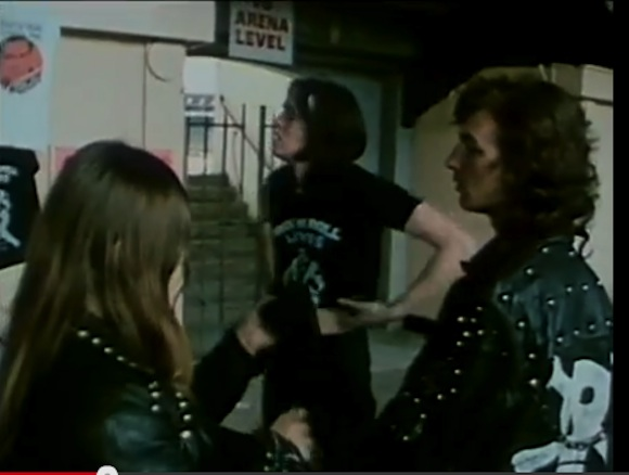 //Customer (centre) tries on Rock N Roll Lives Chuck Berry shirt. Still from Peter Clifton's London Rock N Roll Show//