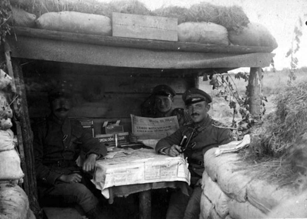 "German troops reading ""The Daily Mail"" in a dugout at Wieltje, East of Ypres, 1915."