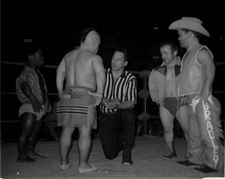 Referee George Gadaski talks to the legendary Little Beaver (back to camera) with tag partner Jamaica Kid to his left, and rivals Billy the Kid and Cowboy Bradley to his right.