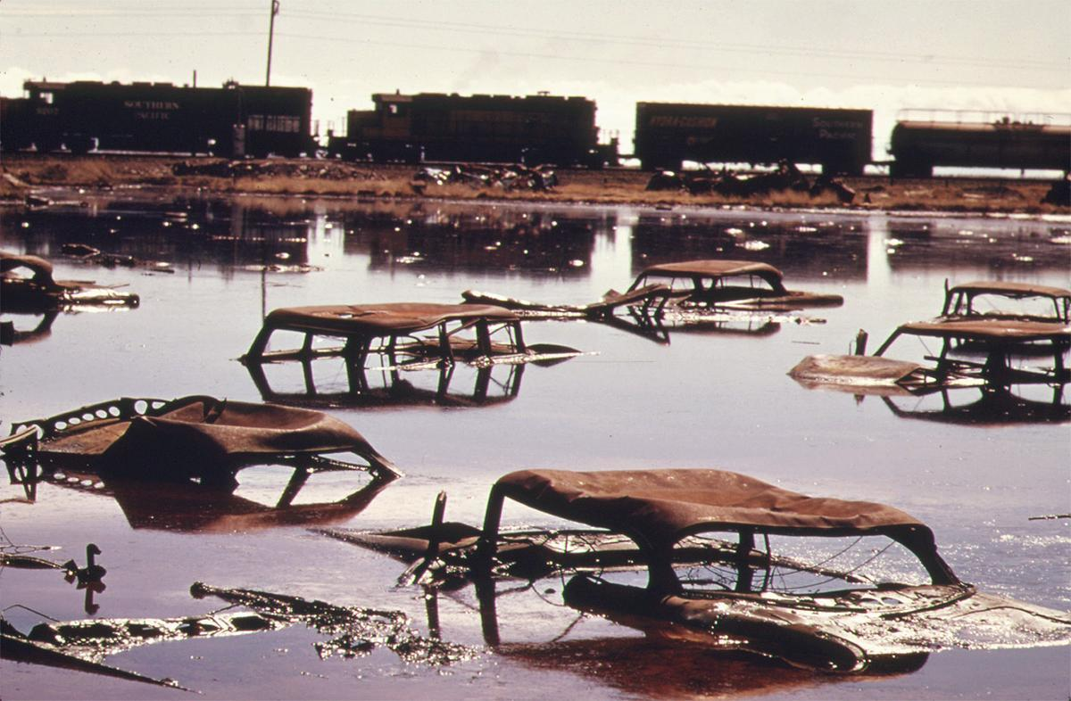 A train on the Southern Pacific Railroad passes a five-acre pond, which was used as a dump site by area commercial firms, near Ogden, Utah, in April of 1974. The acid water, oil, acid clay sludge, dead animals, junked cars and other dump debris were cleaned up by several governmental groups under the supervision of the EPA. Some 1,200,000 gallons of liquid were pumped from the site, neutralized and taken to a disposal site. # Bruce McAllister/NARA