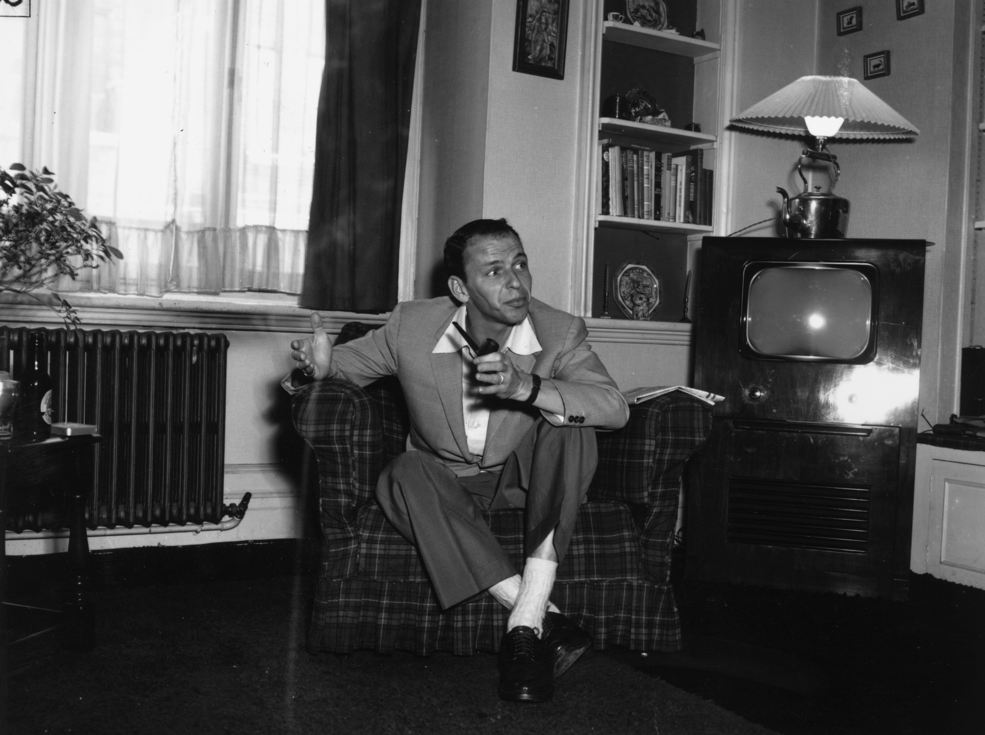 29th June 1953: Popular American singer Frank Sinatra relaxing with a pipe at his flat in Mayfair, London, before his concert at the Palladium. (Photo by R. Mitchell/Express/Getty Images)