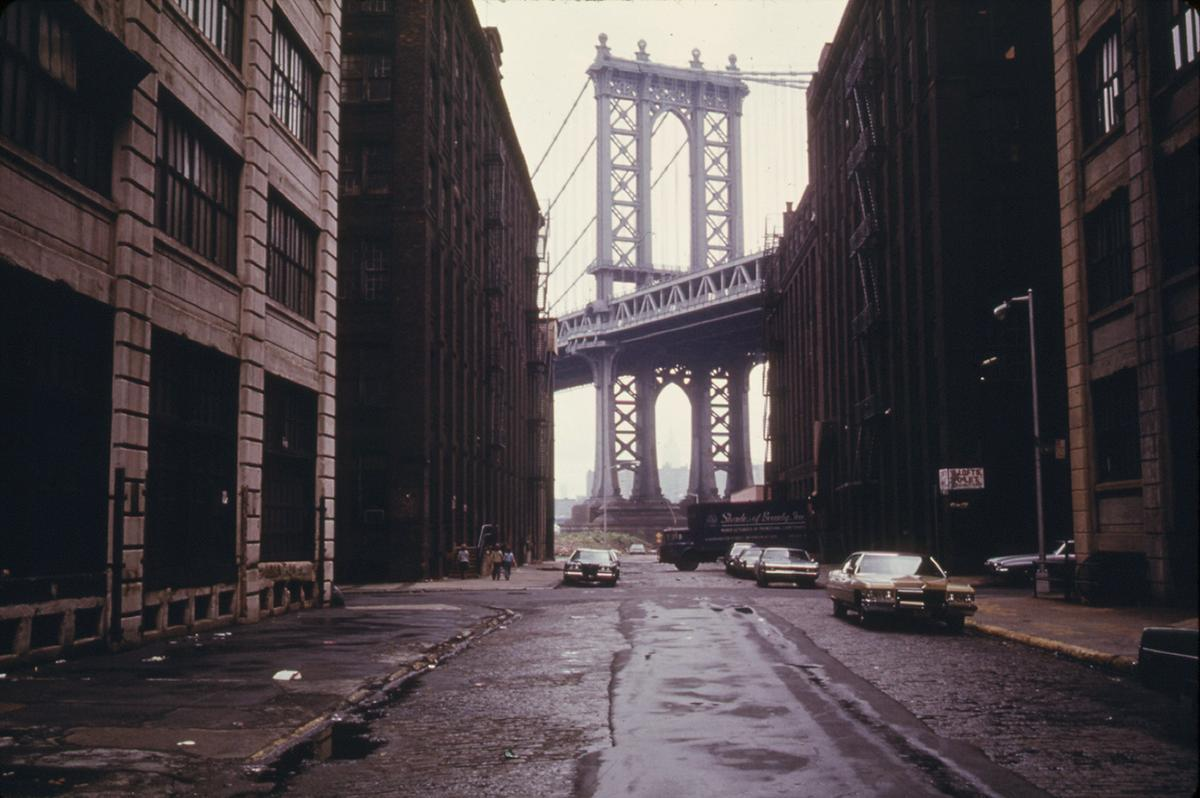 Manhattan Bridge tower in Brooklyn, New York City, framed through nearby buildings, in June of 1974. # Danny Lyon/NARA