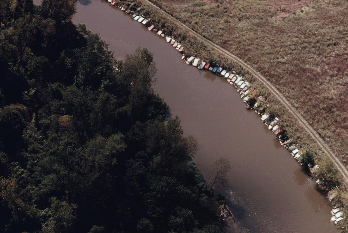 An aerial view of old cars secured along a bank of the Cuyahoga River to prevent erosion at Jaite North of Peninsula, Ohio, near Cleveland, seen in September of 1975. The river passes through private property at this point. The river and valley are part of the newly created Cuyahoga Valley National Recreation Area, a 20-mile stretch of largely undeveloped land between the metropolitan districts of Cleveland and Akron. # Frank J. Aleksandrowicz/NARA
