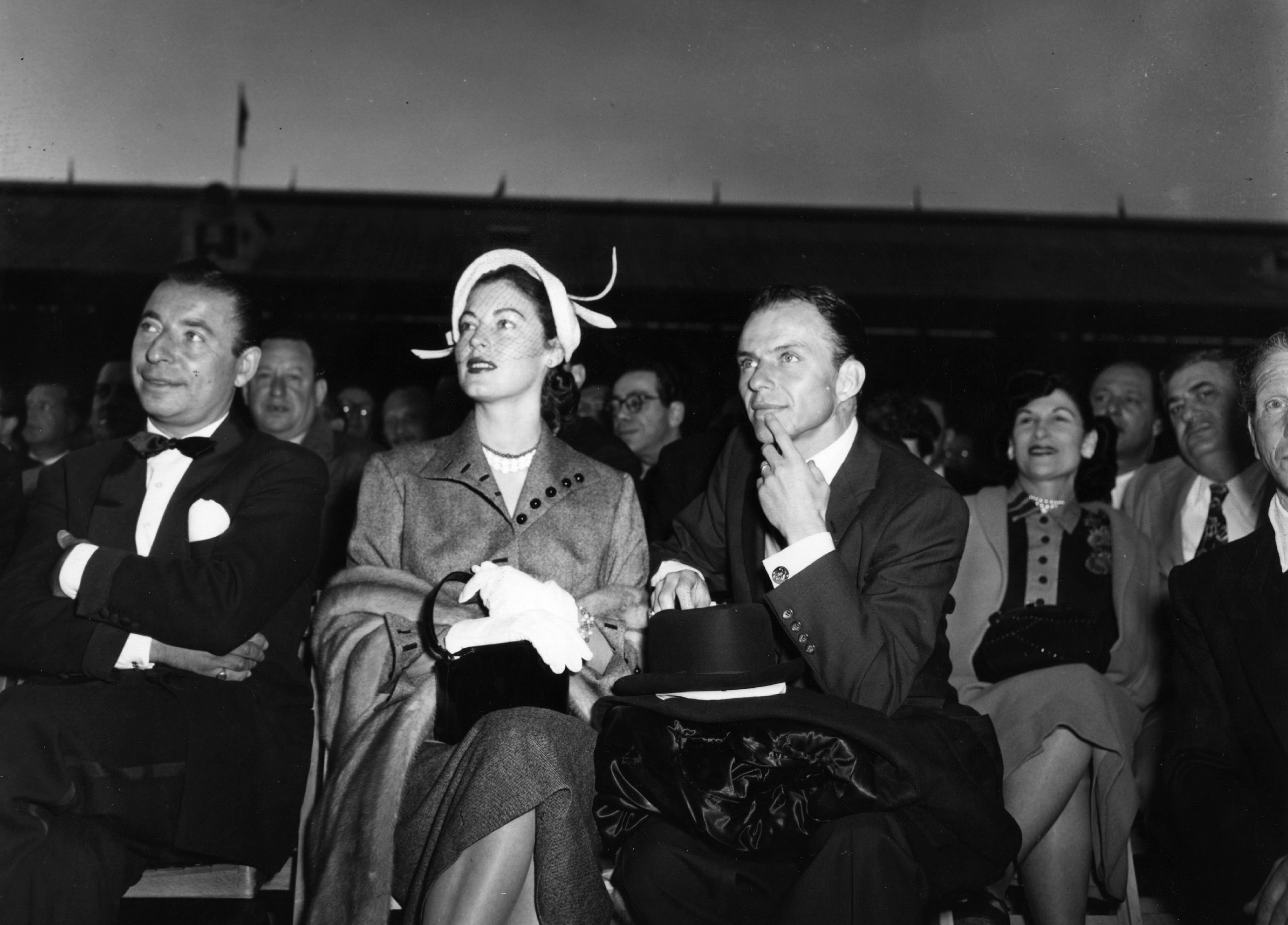 9th June 1953: Actress Ava Gardner, actor and singer Frank Sinatra (right) and band leader Joe Loss in the front row at White City Stadium to watch Randolph Turpin fight Charles Homez for the World Middleweight Boxing title. (Photo by Topical Press Agency/Getty Images)