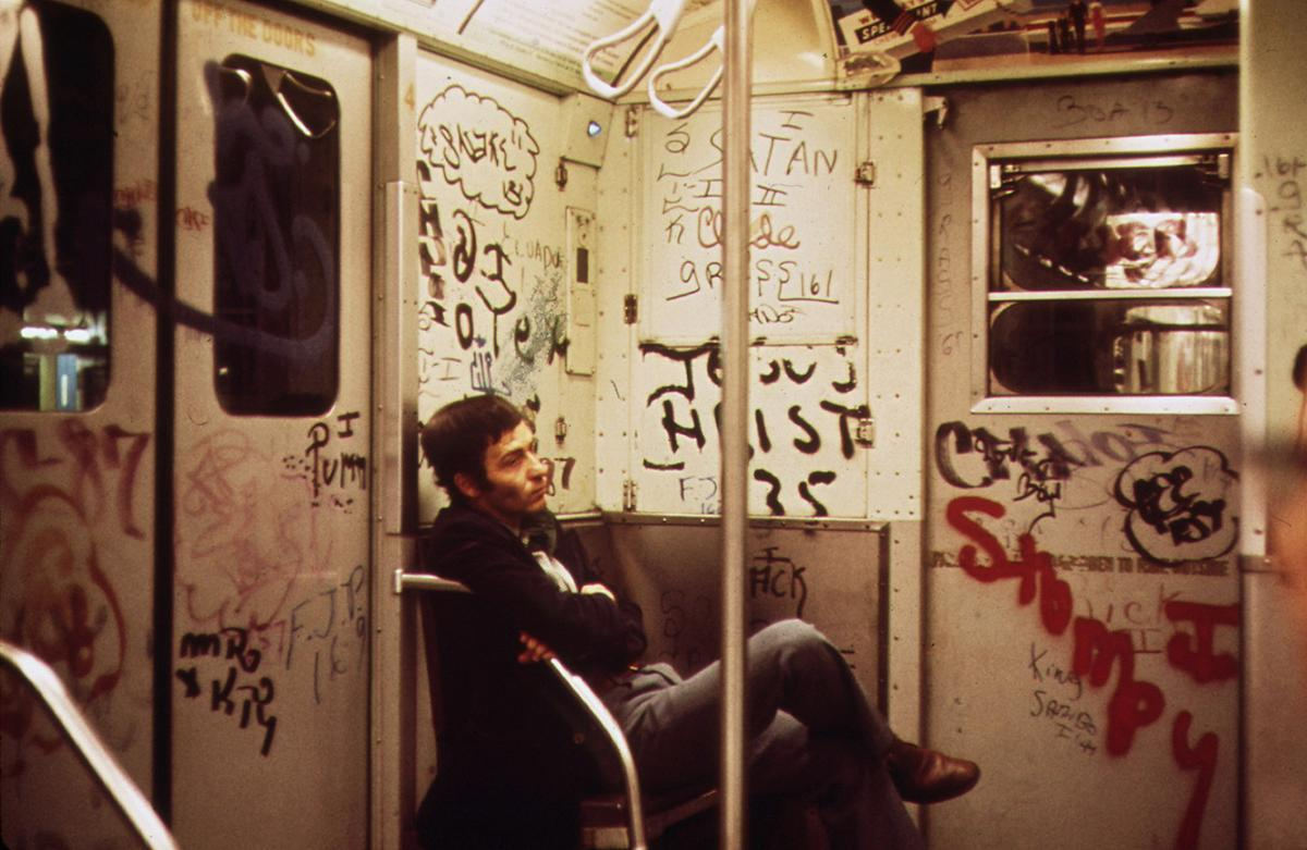 A man rides in a graffiti-covered subway car in New York City in May of 1973. # Erik Calonius:NARA
