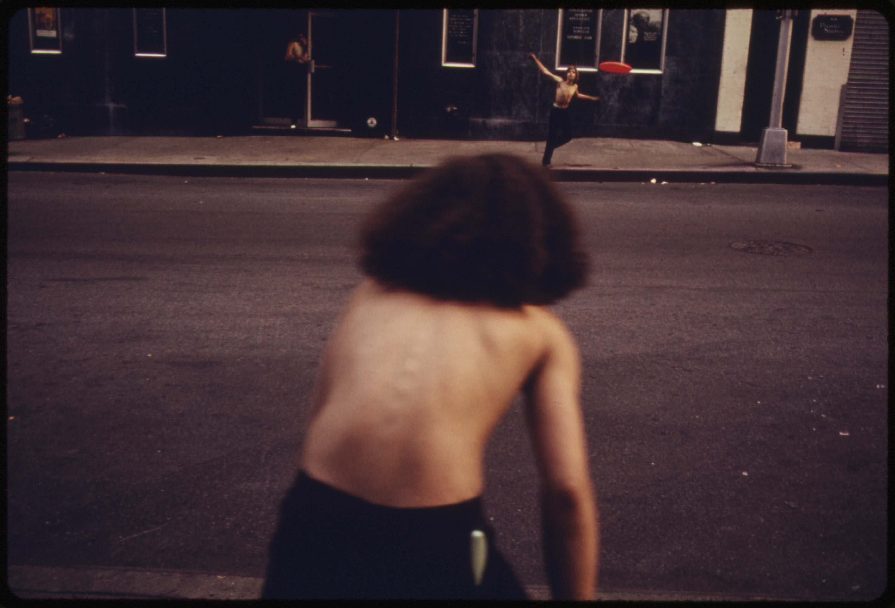 Boys playing frisbee across West 46th Street in Manhattan, July 1974.