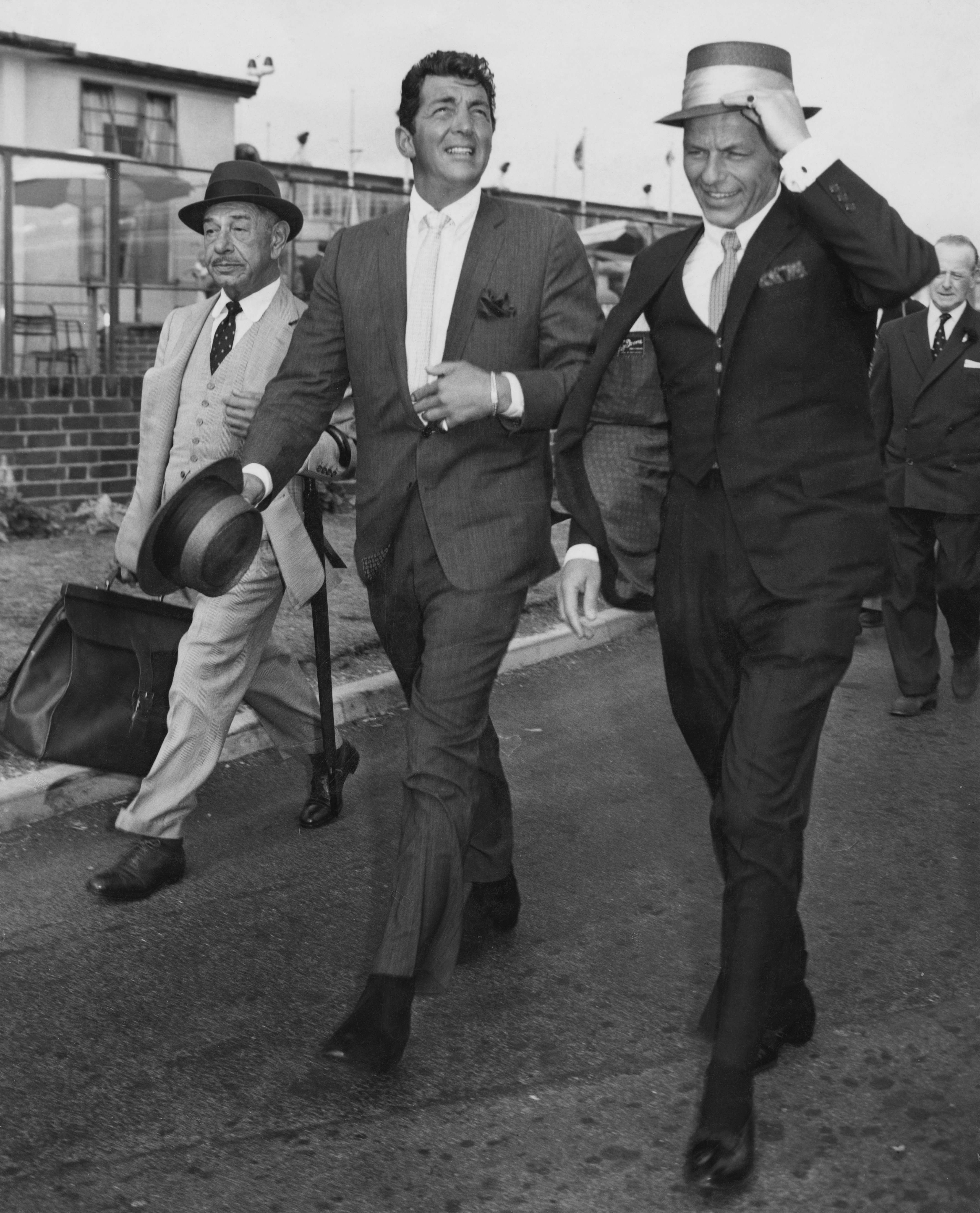 American singers and actors Dean Martin (1917 - 1995) (centre) and Frank Sinatra (right) arriving at London airport, their friend and famed Beverly Hills restauranteur Mike Romanoff is with them. (Photo by J Wilds/Getty Images)