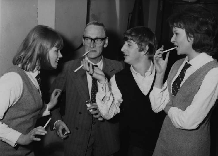 "Cigarettes all around as Beatles drummer Ringo Starr, second from right, chats with actress Susan Boyd, left, actor Wilfred Brammel, and Tina Williams on the set of the Beatles first film, (not yet named) at Twickenham Studios, near London, Middlesex, March 12, 1964. EDS note: The movie was later given the title ""Yeah! Yeah! Yeah! (AP Photo)"
