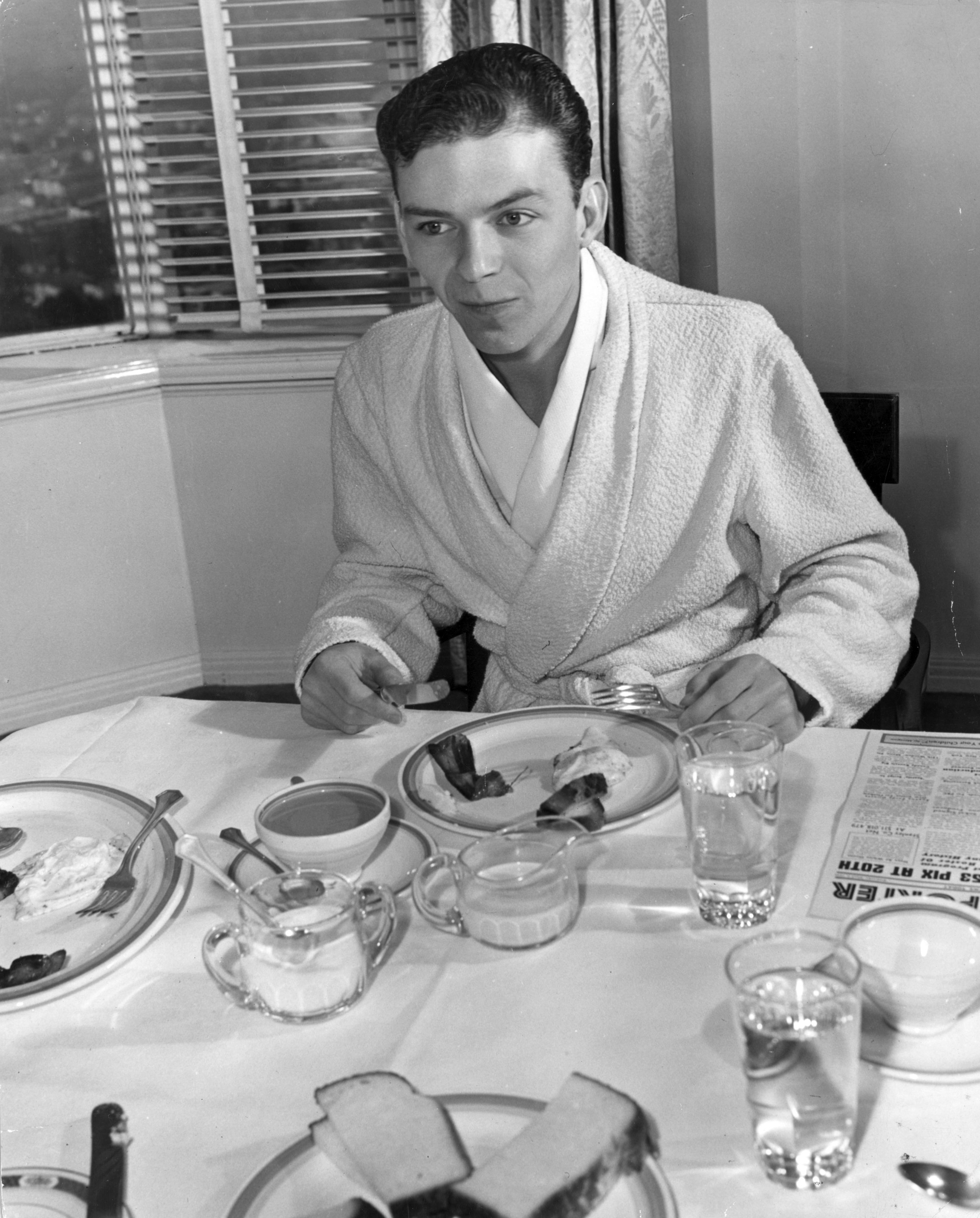 circa 1940: A young Frank Sinatra in his dressing gown tucks into some bacon and eggs. (Photo by Hulton Archive/Getty Images)