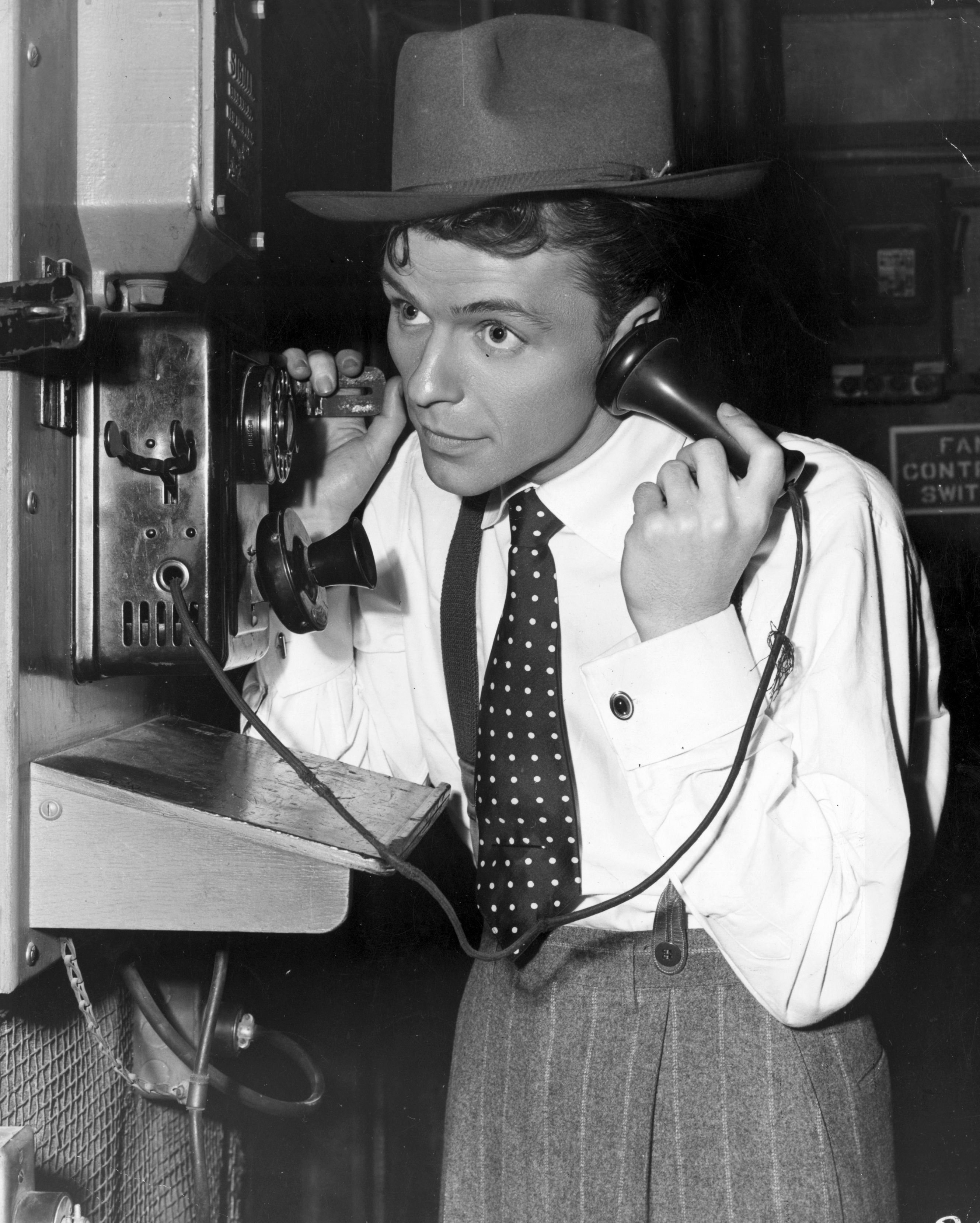 circa 1940: A young Frank Sinatra making a telephone call on the set of the film 'Step Lively'. (Photo by Hulton Archive/Getty Images)