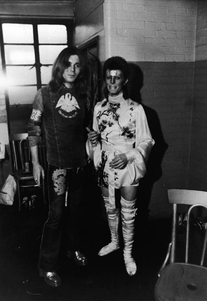 British rock singer David Bowie wears his costume and makeup as 'Ziggy Stardust,' standing backstage beside his makeup artist Pierre Laroche, 1973. (Photo by Express Newspapers/Getty Images)