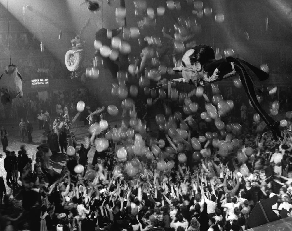 A huge caricature of conductor Sir Malcolm Sargent floating above the crowd of New Year revellers at the Chelsea Arts Ball. (Photo by Keystone/Getty Images)