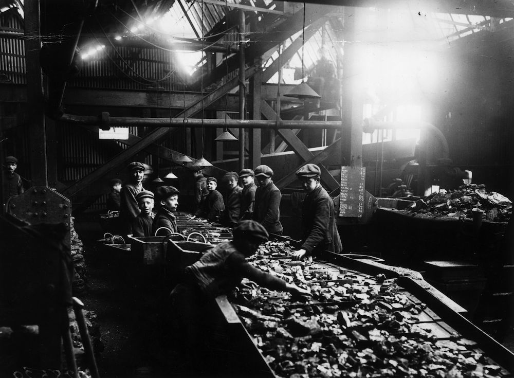 December 1910: Young boys at work at the troughs used for cleaning coal at a pit in Bargoed, South Wales. (Photo by Topical Press Agency/Getty Images)
