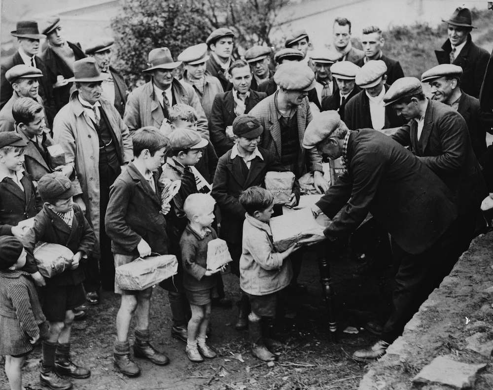 October 1935: Children bring food parcels to miners on strike below ground at the Taff Merthyr colliery in Wales. (Photo by Fox Photos/Getty Images)